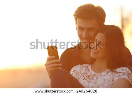 Back light of a happy couple sharing a smart phone in a sunset - stock photo