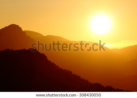 Back light of a sunset on a mountain landscape with a big sun on the sky - stock photo