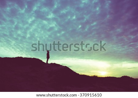 Back light silhouette of a man standing on a hill, overlooking, filtered vintage - future, power, achievement concept - stock photo