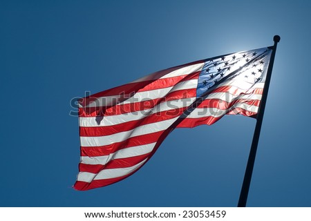 back lighted american flag, clear blue sky - stock photo