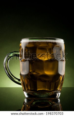 back lit glass mug with beer with reflection