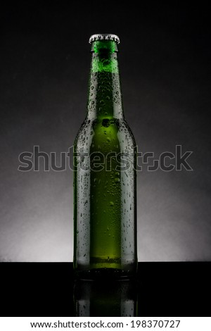 back lit green beer bottle with water drops