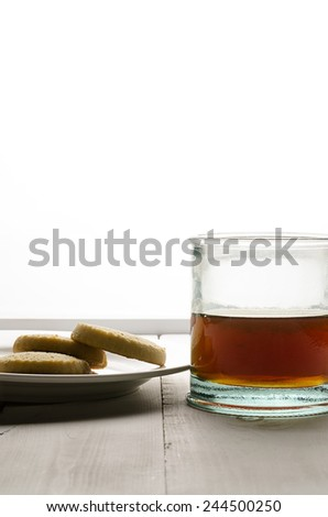 Back lit tea and cookies low center not so close - stock photo