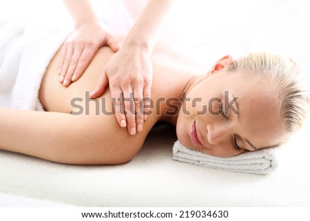 Back massage .Attractive blonde woman in the office spa, relax with a massage  - stock photo