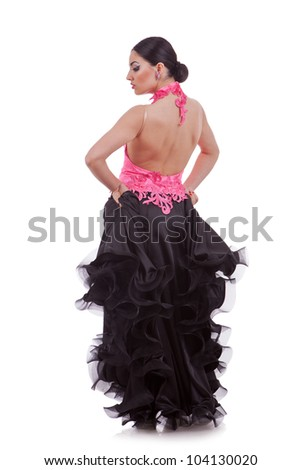 back of a beautiful woman dancer dressed in a beautiful long black and pink dress - stock photo