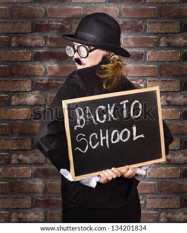 Back of a funny looking headmaster holding black board with back to school written in chalk. School brick wall background - stock photo
