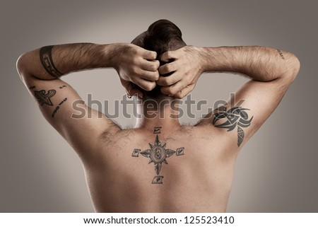 back of a guy with a lot of tattoos and a mohawk style hair - stock photo