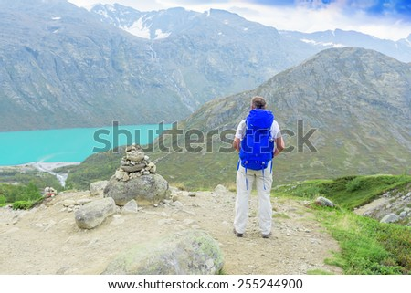Back of a man with blue backpack in mountains looking away - stock photo