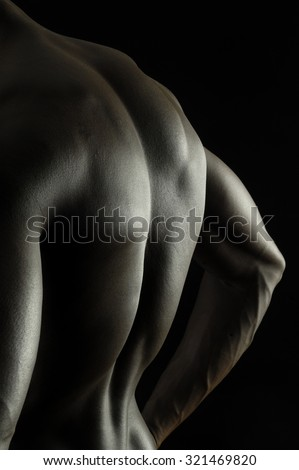back of a naked African boy, black background