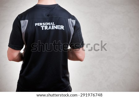 Back of a Personal Trainer isolated in grey - stock photo