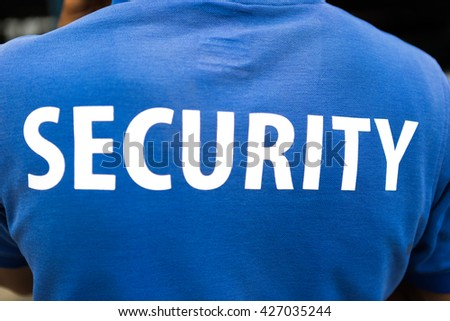 back of a security guards on blue tee shirt