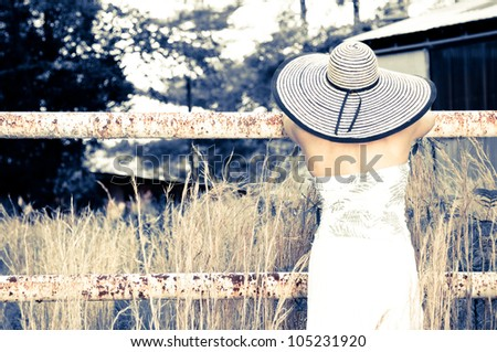 Back of a Woman wearing a big hat leaning on a rusted fence. Photo in