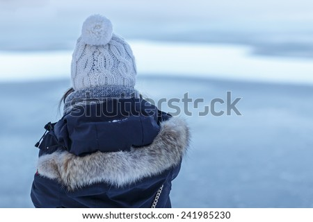 Back of a young woman in think winter clothes as she looks towards a frozen lake. - stock photo