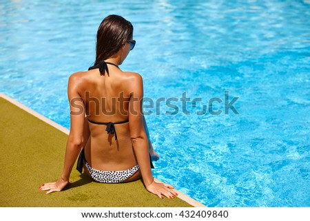 Back of beautiful elegant tanned woman relaxing in bikini and sunglasses in swimming pool spa. Portrait in hot summer day and bright sunny light. - stock photo