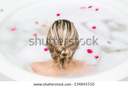 Back of blonde woman taking a foam bath