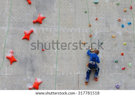 Back of boy climbing with rope on special wall for climbing outdoor - stock photo