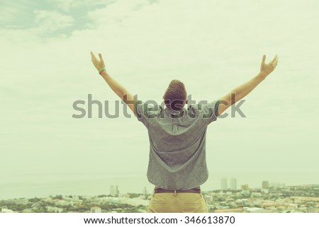 Back of business man standing on the top of mountain, raise hand in vintage tone. - stock photo