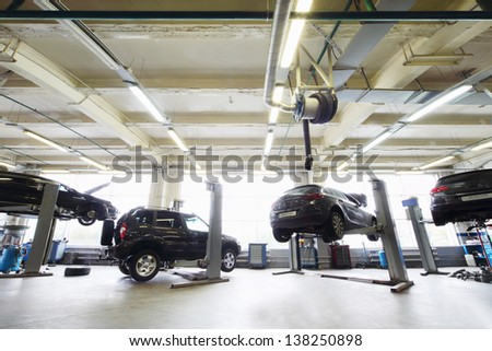 Back of four black cars in garage with special equipment for repair. - stock photo