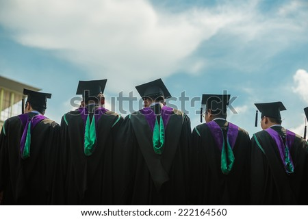 Back of graduates with blue sky