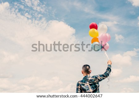 back of Happy young hipster man holding colorful balloons in grassland enjoy life and happy.