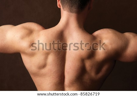 Back of muscular man, isolated on dark background