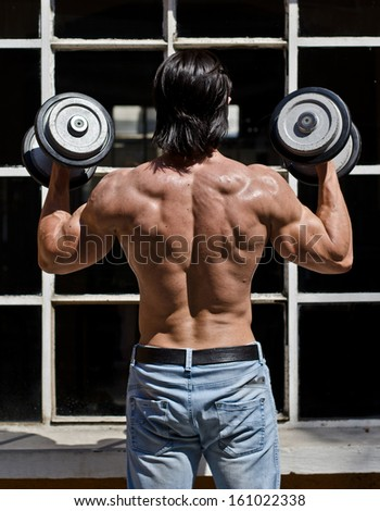 Back of muscular young bodybuilder shirtless outdoors in jeans, exercising biceps with dumbbells - stock photo