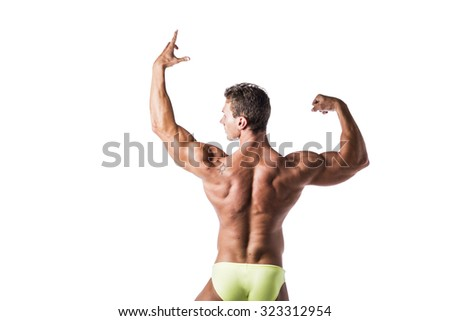 Back of muscular young man standing and looking to a side, shirtless, doing bodybuilding pose, wearing underwear - stock photo