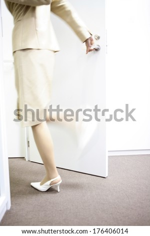 Back of office lady opening the door in a hurry