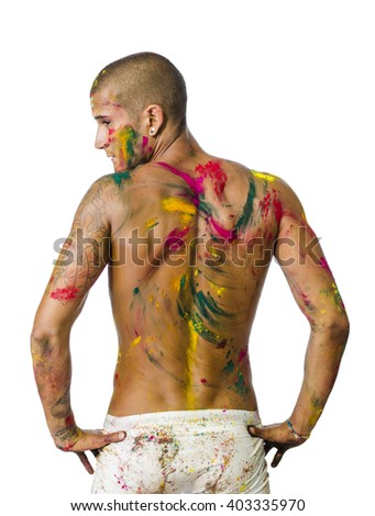 Back of shirtless young man, skin painted all over with bright Holi colors