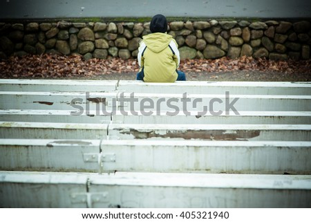Back of single lonely child in coat and hat sitting on painted white bench near wall of stones with copy space - stock photo