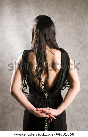 Back of the beautiful woman in a black dress and with a sword. - stock photo