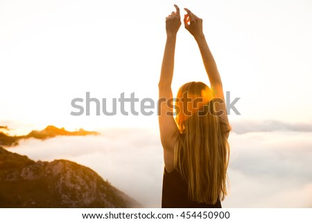 Back of the girl looking at the sunset in a mountain
