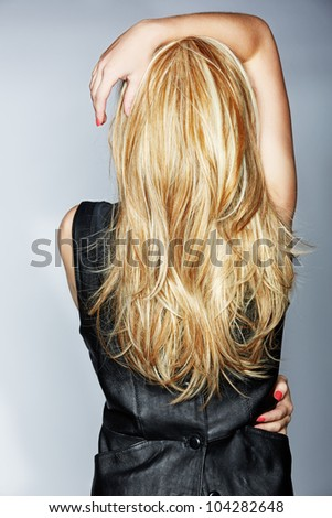 back of the torso a woman with thick long honey blond hair wearing black leather dress on studio background - stock photo