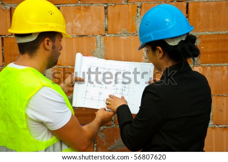 Back of two architects with helmet working in a house under construction and holding blueprints,selective focus on plan - stock photo