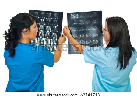 Back of two doctors women compare results of MRI and having conversation isolated on white background - stock photo