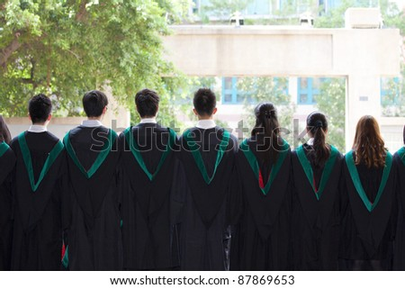 Back of university graduates with their gowns - stock photo