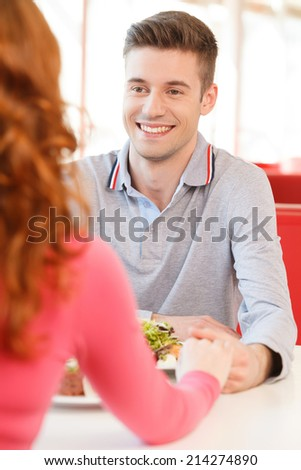back of woman holding biyfriend's hand at restaurant. man's and woman's hands on table in cafe  - stock photo