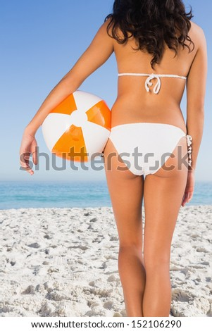Back of woman's perfect body holding beach ball on the beach