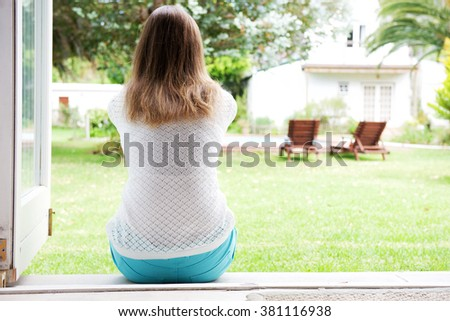 Back of woman sitting and looking outside of home - stock photo