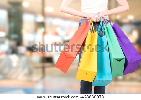 back of women holding shopping bag and decision to go to shop - stock photo