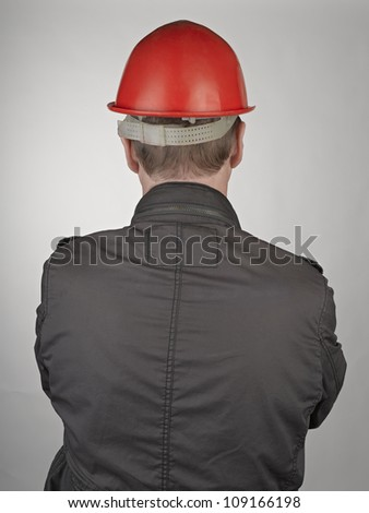 Back of worker man on grey background - stock photo
