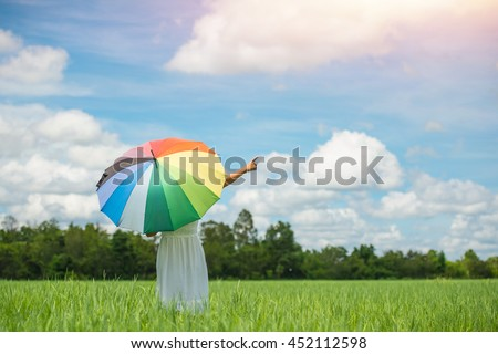 Back Of Young Beautiful woman holding multicolored umbrella in green grassland field and cloud blue sky.