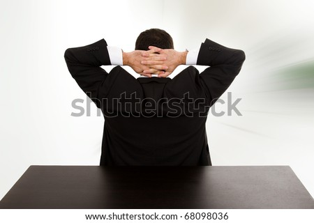 Back of young businessman relaxing on the desk at the office - stock photo