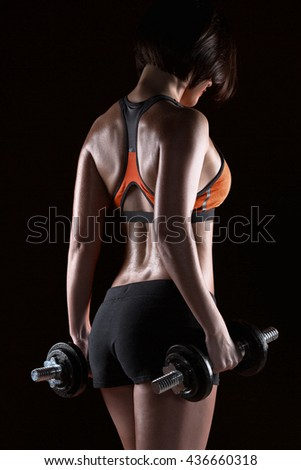 back of young fitness girls with dumbbells