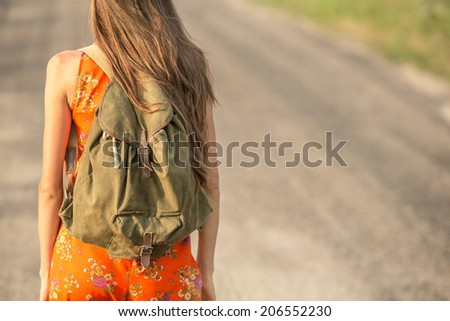 Back of young hipster woman with backpack. focus on backpack - stock photo