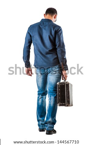 back of young man in a blue shirt and jeans holding a suitcase in his hand isolated on white background - stock photo