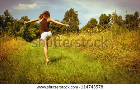 Back of young woman skipping down nature walk way - stock photo