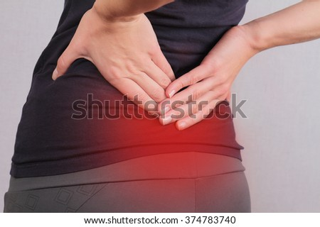 Back Pain. Athletic fitness woman rubbing the muscles of her lower back. Sports exercising injury. - stock photo