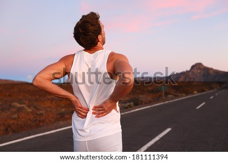 Back pain. Athletic running man with injury in sportswear rubbing touching lower back muscles standing on road outside at night. - stock photo