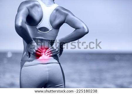 Back pain. Athletic running woman with back injury in sportswear rubbing touching lower back muscles standing on road outside. - stock photo